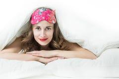 Schöne Frau, die auf dem Bett liegt stockfotografie