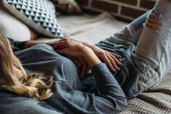 junge erwachsene heterosexuelle paare die auf bett im schlafzimmer liegen stockfoto bild von. Black Bedroom Furniture Sets. Home Design Ideas