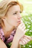 Schöne Frau, die auf dem Gras mit Blumen liegt Stockfotos