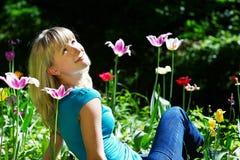 Schöne Frau, die auf dem Gras unter Blumen sitzt Lizenzfreies Stockfoto