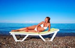Schöne Frau, die auf dem Strand sich entspannt Lizenzfreie Stockfotos