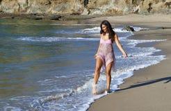 Schöne Frau, die auf den Strand geht stockfoto