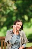 Schöne Frau, die auf der Bank anruft Lizenzfreies Stockbild