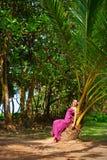 Schöne Frau, die auf der Palme sitzt Lizenzfreie Stockfotos