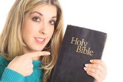 Schöne Frau, die auf die Bibel zeigt Stockfotografie