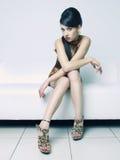 Schöne Frau, die auf einem Sofa sitzt Stockfotografie