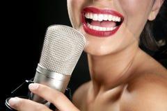 Schöne Frau, die auf einem Weinlesemikrofon singt Stockbild