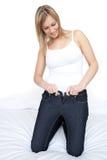 Schöne Frau, die auf feste Jeans auf einem Bett sich setzt Lizenzfreie Stockbilder