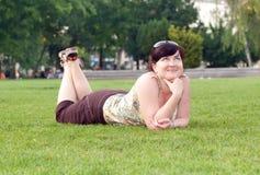 Schöne Frau, die auf Gras liegt stockfotografie