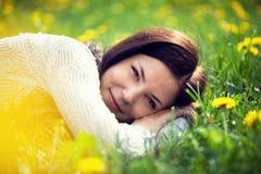 Schöne Frau, die auf Gras liegt Lizenzfreies Stockbild