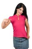 Schöne Frau, die auf ihr rosafarbenes unbelegtes T-Shirt zeigt Lizenzfreie Stockfotos