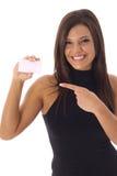 Schöne Frau, die auf Visitenkarte zeigt Stockfotografie