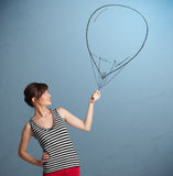 Schöne Frau, die Ballonzeichnung anhält Lizenzfreie Stockfotos