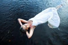 Schöne Frau, die in blauen Fluss schwimmt Lizenzfreie Stockfotos