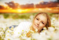 Schöne Frau, die Blumenfeld auf Sonnenuntergang genießt Lizenzfreie Stockfotos