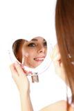 Schöne Frau, die Creme auf Gesicht auf weißem Hintergrund aufträgt stockfotografie