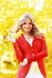 Schöne Frau, die in den Wald an einem Falltag geht Stockfotografie