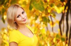 Schöne Frau, die in den Wald an einem Falltag geht Blonde Mädchen-und Gelb-Blätter Porträt Stockfotografie