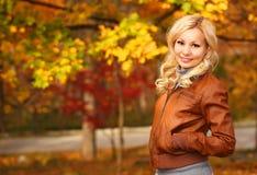 Schöne Frau, die in den Wald an einem Falltag geht Fall Blondes Mädchen mit Blättern lizenzfreies stockbild