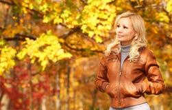 Schöne Frau, die in den Wald an einem Falltag geht Fall Blondes Mädchen mit gelben Blättern Lizenzfreies Stockbild