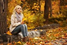 Schöne Frau, die in den Wald an einem Falltag geht Fall Blondes schönes Mädchen mit gelben Blättern Lizenzfreie Stockfotos