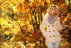 Schöne Frau, die in den Wald an einem Falltag geht Fall Blondes schönes Mädchen mit gelben Blättern Stockfotos