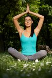 Schöne Frau, die in der Yogahaltung im Park meditiert stockfotografie