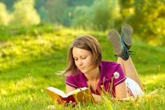 Schöne Frau, die ein Buch genießt Lizenzfreies Stockfoto
