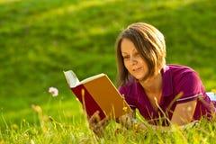 Schöne Frau, die ein Buch im Park liest Stockbild