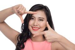 Schöne Frau, die ein Feld mit den Fingern vor Gesicht bildet stockbild