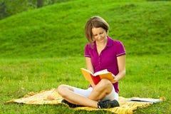 Schöne Frau, die ein lustiges Buch, horizontal genießt Stockfotos
