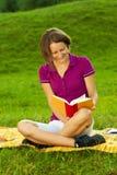 Schöne Frau, die ein lustiges Buch, vertikal genießt Lizenzfreie Stockfotografie