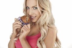 Schöne Frau, die ein Muffin isst Stockfotos
