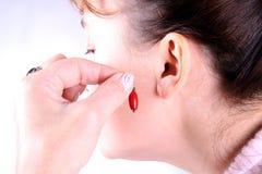 Schöne Frau, die ein Ohrring setzt Lizenzfreie Stockfotografie