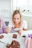 Schöne Frau, die ein Stück des Schokoladenkuchens isst Lizenzfreie Stockbilder