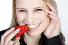 Schöne Frau, die eine Erdbeere isst Stockfotos