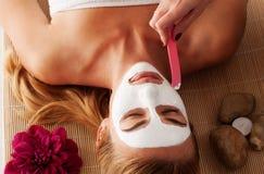Schöne Frau, die eine Gesichtsmaske hat Stockbilder