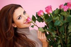 Schöne Frau, die eine Rose riecht Stockfotografie
