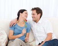 Schöne Frau, die eine Rose sitzt auf dem Sofa anhält Lizenzfreie Stockfotos