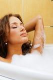 Schöne Frau, die in einem Bad sich entspannt Lizenzfreie Stockfotos