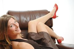 Schöne Frau, die in einem Sessel sitzt Stockfoto
