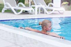 Schöne Frau, die in einem Swimmingpool sich entspannt Stockfoto