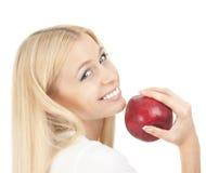 Schöne Frau, die einen roten Apfel beißt Stockfotografie