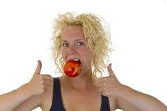 Schöne Frau, die in einen roten saftigen Apfel beißt Lizenzfreies Stockfoto