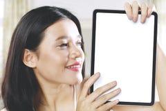 Schöne Frau, die einen unbelegten Vorstand anhält stockbilder