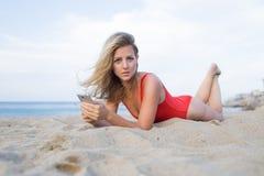 Schöne Frau, die Fotos auf einem Smartphone während der Sommerferienfeiertage Meer betrachtet Stockfotos