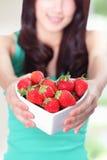 Schöne Frau, die frische Erdbeeren zeigt stockfotografie