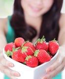 Schöne Frau, die frische Erdbeeren zeigt lizenzfreies stockbild