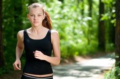 Schöne Frau, die in grünen Park läuft Stockfotos