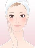 Schöne Frau, die ihr Gesicht nach Hautsorgfalt berührt Stockbilder